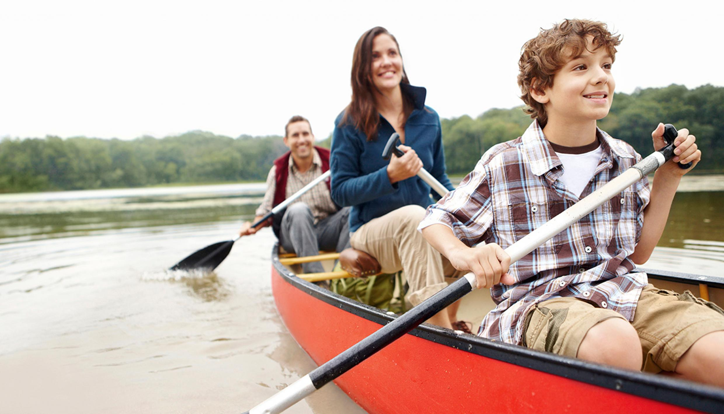 A family paddles in a canoe on a quiet lake