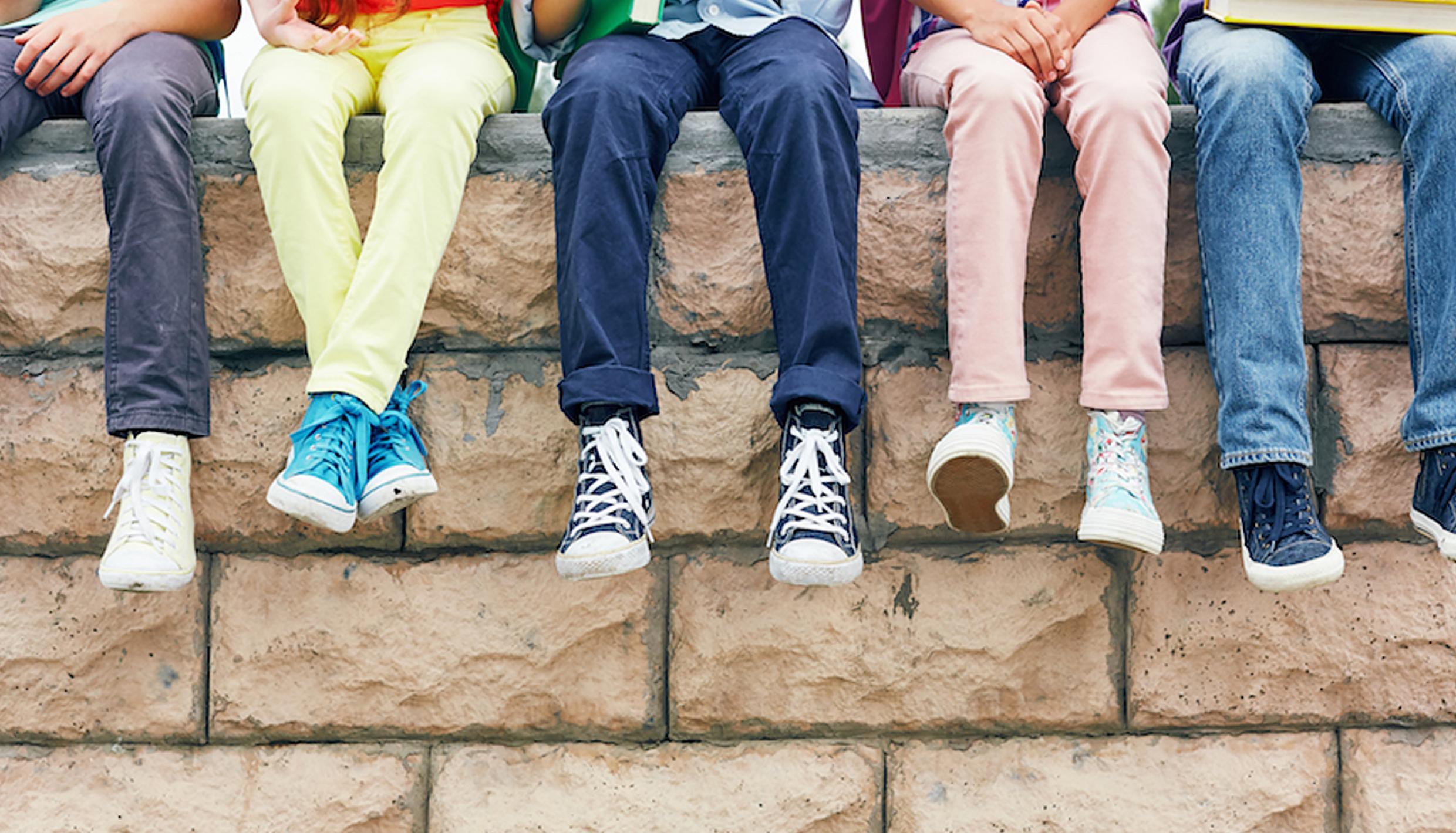 A row of kids dangling their legs over a low wall