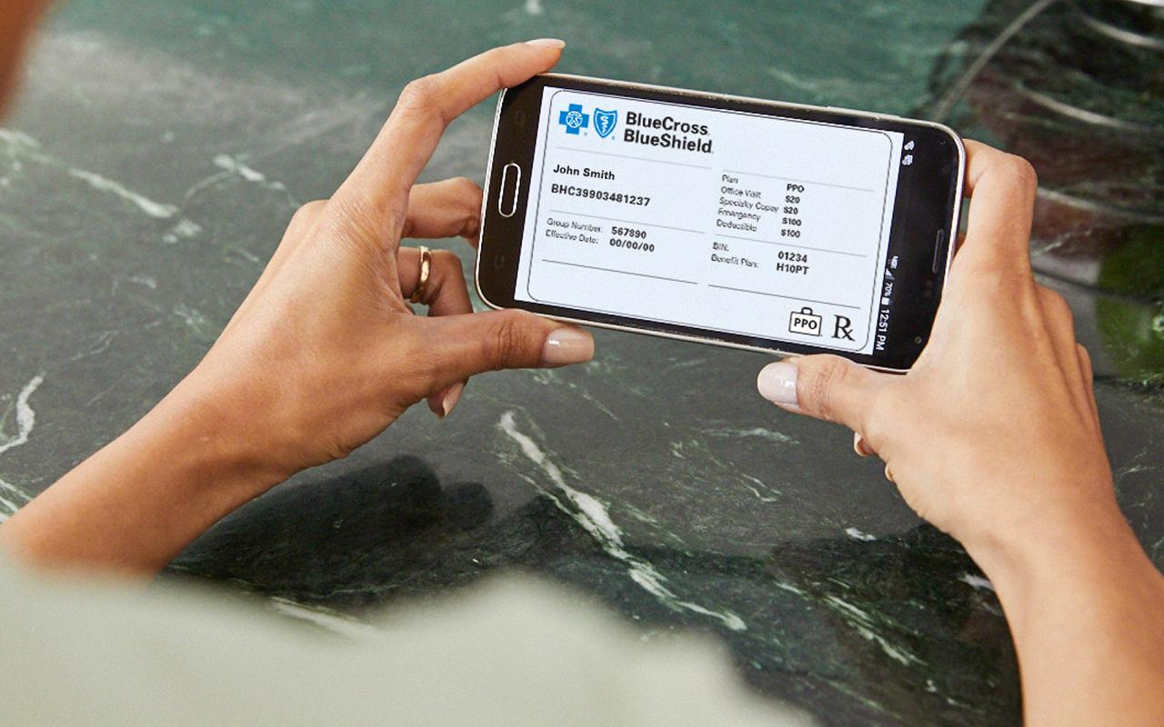 Person holding a smartphone with a picture of their insurance card displayed