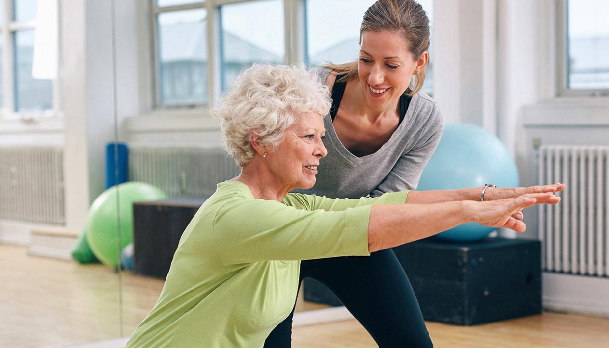 Older woman performing yoga stretches with a young trainer