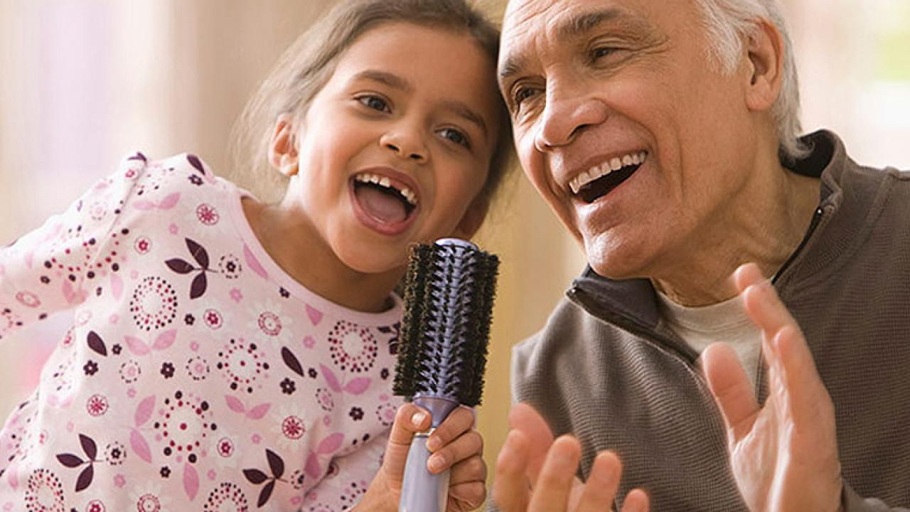 Grandpa and Granddaughter signing with a hairbrush microphone