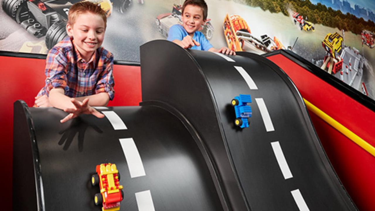 Two boys sliding Lego cars down a toy street ramp
