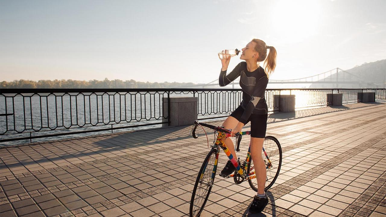 Woman on a bike drinking water