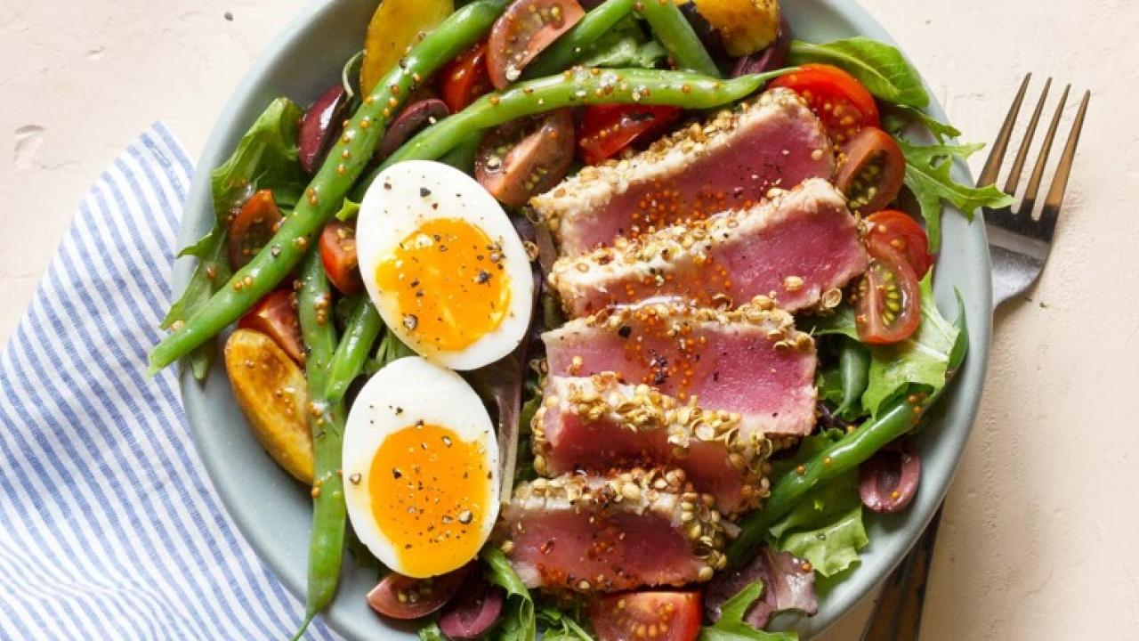 Ahi tuna and a hard boiled egg on a plate of veggies