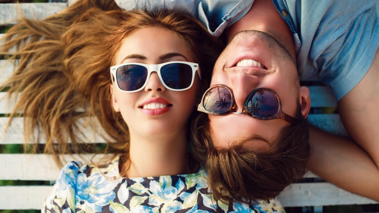 Man and woman laying down wearing sunglasses