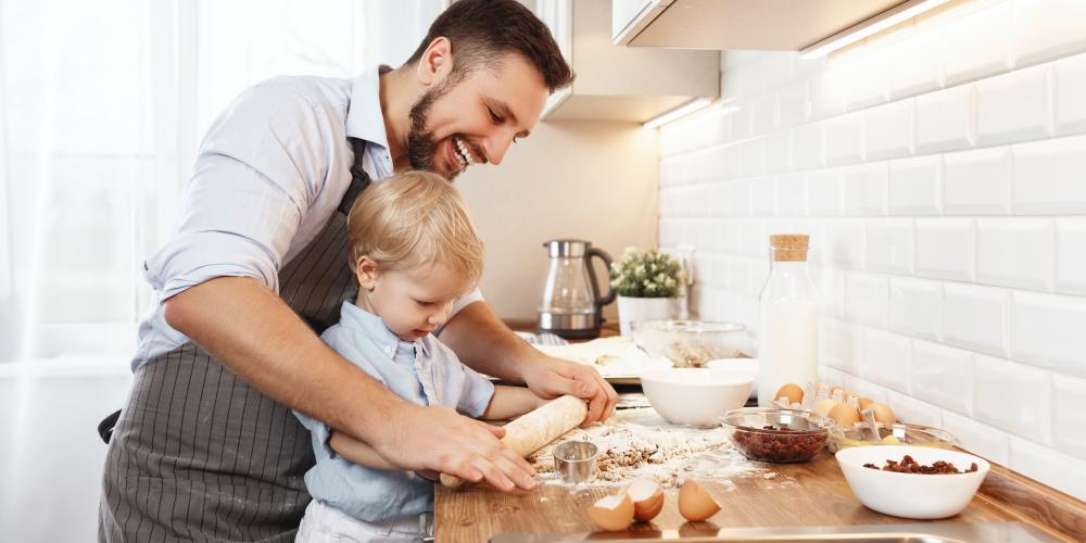 A father helping his son cook in the kitchen