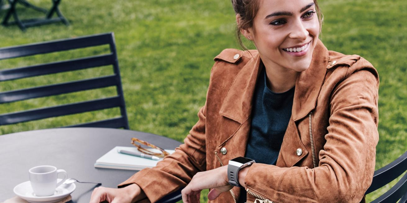 A woman at a cafe table wearing a soft brown leather jacket and with a smart watch on her wrist