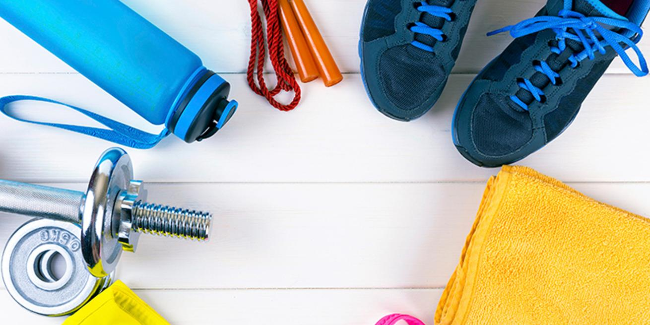 An array of workout items, such as a barbell, water bottle, jumprope, yoga mat, and sneakers